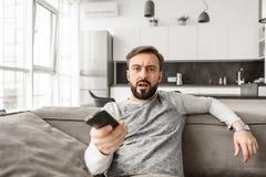 Portret van een geschokte afstandsbediening van TV van de jonge mensenholding Royalty-vrije Stock Afbeeldingen