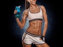 Portret van een gezond jong vrouwen drinkwater tegen een grung royalty-vrije stock afbeeldingen