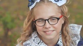 Portret van een glimlachend 13 éénjarigenmeisje met glazen Dichte omhooggaand van het gezicht stock video