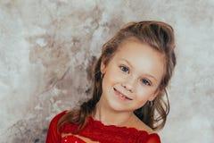 Portret van een glimlachend jong meisje in een rode kleding en met een mooi kapsel Het schot van de studio royalty-vrije stock afbeeldingen