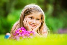 Portret van een glimlachend meisje dat op groen gras ligt Royalty-vrije Stock Foto