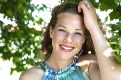 Portret van een glimlachend meisje in de bladeren royalty-vrije stock afbeelding