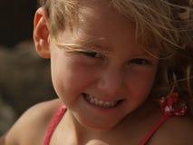 Portret van een glimlachend meisje met blond haar dat zich in de wind ontwikkelt stock fotografie