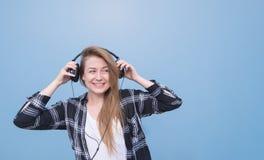 Portret van een glimlachend meisje in zich op een blauwe achtergrond bevinden, aan muziek luisteren en vrijetijdskleding die weg  stock afbeelding