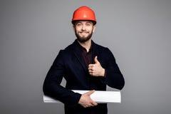 Portret van een glimlachende architect in bouwvakker met blauwdruk gesturing duimen omhoog op grijs royalty-vrije stock fotografie