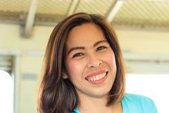 Portret van een glimlachende Aziatische vrouw op een trein stock foto
