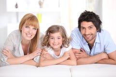 Portret van een glimlachende familie die op een bed wordt gelegd Stock Foto's