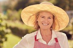 Portret van een glimlachende hogere vrouw in strohoed in openlucht royalty-vrije stock fotografie