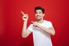 Portret van een glimlachende jonge mens in het witte t-shirt richten stock foto's