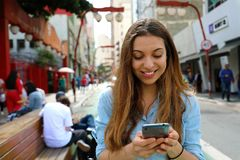 Portret van een glimlachende jonge vrouw die in Sao Paulo City met cellphone lopen, Brazilië stock afbeeldingen
