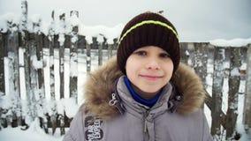 Portret van een glimlachende jongen in de winter stock footage