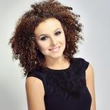 Portret van een glimlachende krullende haired vrouw Royalty-vrije Stock Afbeeldingen