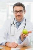 Portret van een glimlachende mannelijke arts die een appel houden Stock Foto's