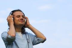 Portret van een glimlachende mens met oortelefoons royalty-vrije stock fotografie