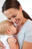 Portret van een glimlachende moeder die leuk babymeisje koesteren Stock Foto's