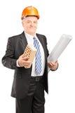 Portret van een glimlachende rijpe architect die een baksteen houden Stock Fotografie