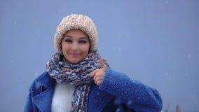 Portret van een glimlachende vrouw die duimen over de winterachtergrond tonen Het concept van de winter Sneeuw en vrouw stock footage