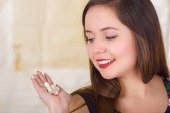 Portret van een glimlachende vrouwenholding in haar hand een zachte gelatine vaginale tablet of een zetpil, behandeling van ziekt royalty-vrije stock fotografie