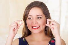 Portret van een glimlachende vrouwenholding in zowel handen een zachte gelatine vaginale tablet of een zetpil, behandeling van zi stock foto