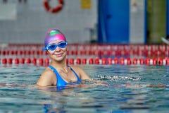 Portret van een glimlachende vrouwenzwemmer in blauw zwempak in de pool na de voltooiing van opleiding stock fotografie