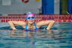 Portret van een glimlachende vrouwenzwemmer in blauw zwempak in de pool na de voltooiing van opleiding stock foto's