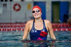 Portret van een glimlachende vrouwenzwemmer in rood blauw zwempak in de pool na de voltooiing van opleiding stock foto's