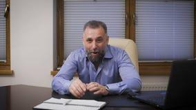 Portret van een goedaardige zakenman Directeur in een blauwe overhemdszitting bij bureau die, die en glimlachen bekijken stock videobeelden