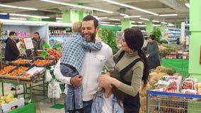 Portret van een grote gelukkige familie in de supermarkt, weinig zoon die zijn papa koesteren stock videobeelden