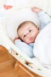 Portret van een heldere baby die in zijn wieg ligt Stock Foto's