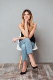 Portret van een het glimlachen aantrekkelijke meisjeszitting op een stoel stock foto's