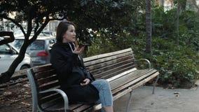 Portret van een het glimlachen hipster meisje het typen bericht op mobiele telefoon terwijl het zitten op bank bij park audioai t stock video