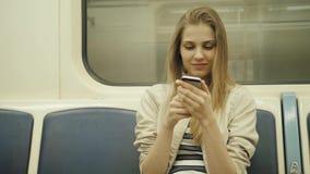 Portret van een het glimlachen mooi meisje het typen bericht op mobiele telefoon in metro, de sexy vrouw van het studentenblonde  stock video