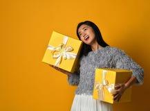 Portret van een het glimlachen mooie die de giftdoos van de meisjesholding over gele achtergrond wordt geïsoleerd royalty-vrije stock foto's