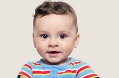 Portret van een het leuke babyjongen zitting en glimlachen stock afbeelding