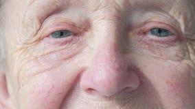 Portret van een hogere Kaukasische vrouw die haar ogen openen stock videobeelden