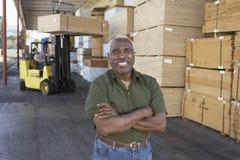 Portret van een Hogere Mens met de Mens die Forktruck op de Achtergrond drijven Royalty-vrije Stock Fotografie