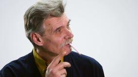 Portret van een hogere mens met sigaret en het denken op witte achtergrond stock videobeelden