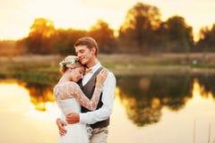 Portret van een huwelijkspaar tegen de achtergrond van het water bij zonsondergangzon Op de achtergrond een meer Stock Afbeeldingen