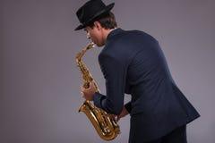 Portret van een jazzmens in een kostuum met hoed het verbergen Stock Foto's
