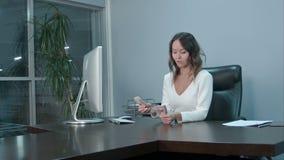 Portret van een jong Aziatisch beambte tellend geld stock video