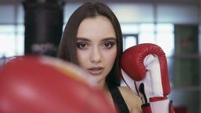 Portret van een jong donkerbruin meisje met bokshandschoenen stock footage