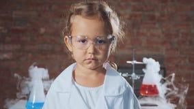 Portret van een jong ernstig meisje van het wetenschapperkind in een chemielaboratorium stock footage