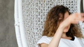 Portret van een jong Europees meisje in een hangmat-schommeling in een zolderflat Mooie vrouw die en in a rusten slingeren stock video
