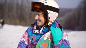 Portret van een jong, gelukkig meisje met een snowboard in haar handen De winter zonnige dag, rond de berg, skitoevlucht A stock video