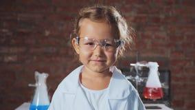 Portret van een jong glimlachend meisje van het wetenschapperkind in een chemielaboratorium stock video