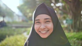 Portret van een jong glimlachend Moslimmeisje in een zwarte hijab stock footage