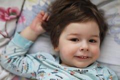 Portret van een jong kind die op een hoofdkussen liggen Stock Foto