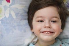 Portret van een jong kind die op een hoofdkussen liggen Stock Foto's