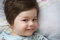 Portret van een jong kind die op een hoofdkussen liggen Stock Afbeelding