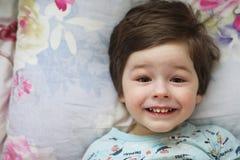 Portret van een jong kind die op een hoofdkussen liggen Stock Afbeeldingen